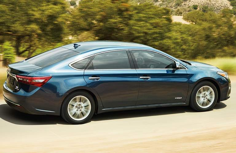blue 2016 Toyota Avalon Hybrid driving on road