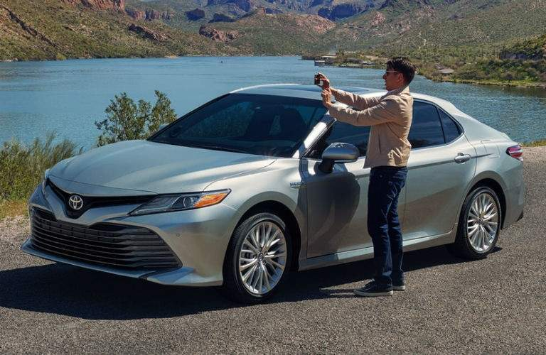 man taking a picture outside of his 2018 Toyota Camry Hybrid
