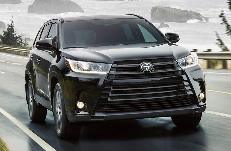 black 2018 Toyota Highlander driving on wet road