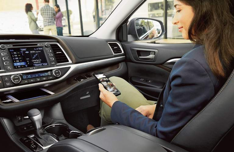 Woman in passenger seat of 2018 Toyota Highlander on her phone