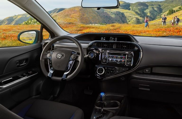 Interior view of a 2018 Toyota Prius c with family out in field