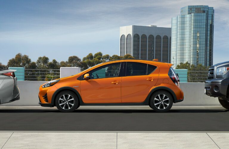 Orange 2018 Toyota Prius c parked between two other vehicles