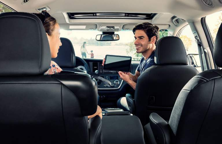 father showing daughter a tablet in the 2018 Toyota Sienna