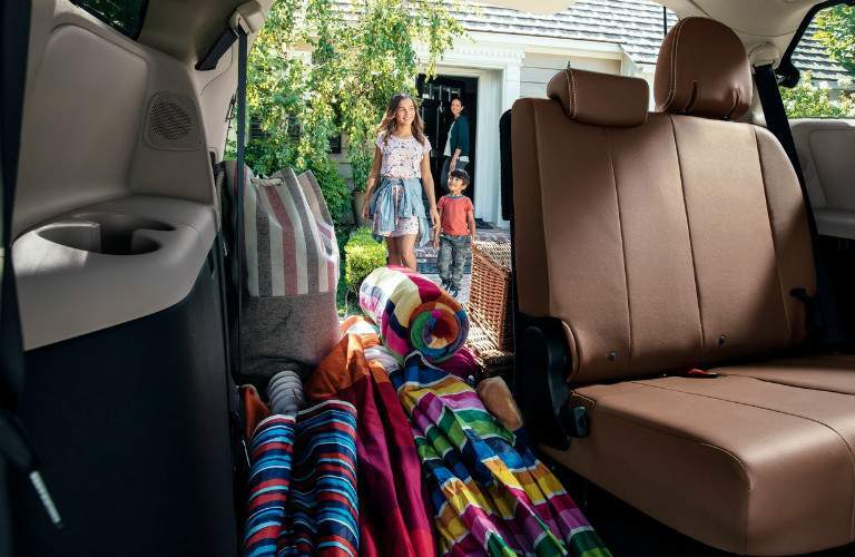 family walking towards 2018 Toyota Sienna filled with gear