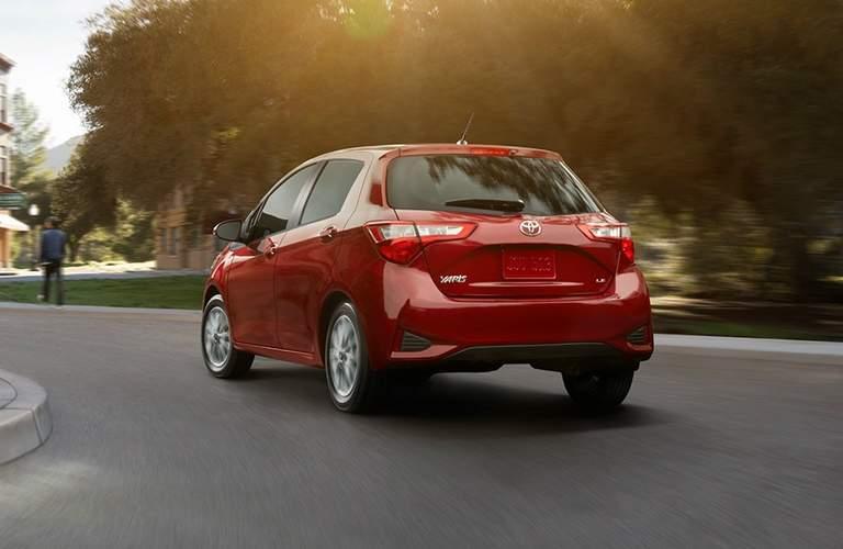 red 2018 Toyota Yaris driving around a corner