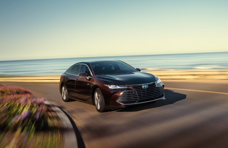 Maroon 2019 Toyota Avalon Hybrid making a right turn