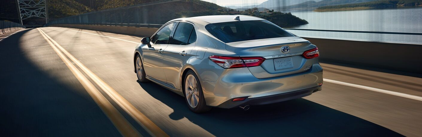 Silver 2019 Toyota Camry Hybrid driving along bridge