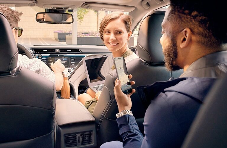 Friends talking while riding in the 2019 Toyota Camry Hybrid