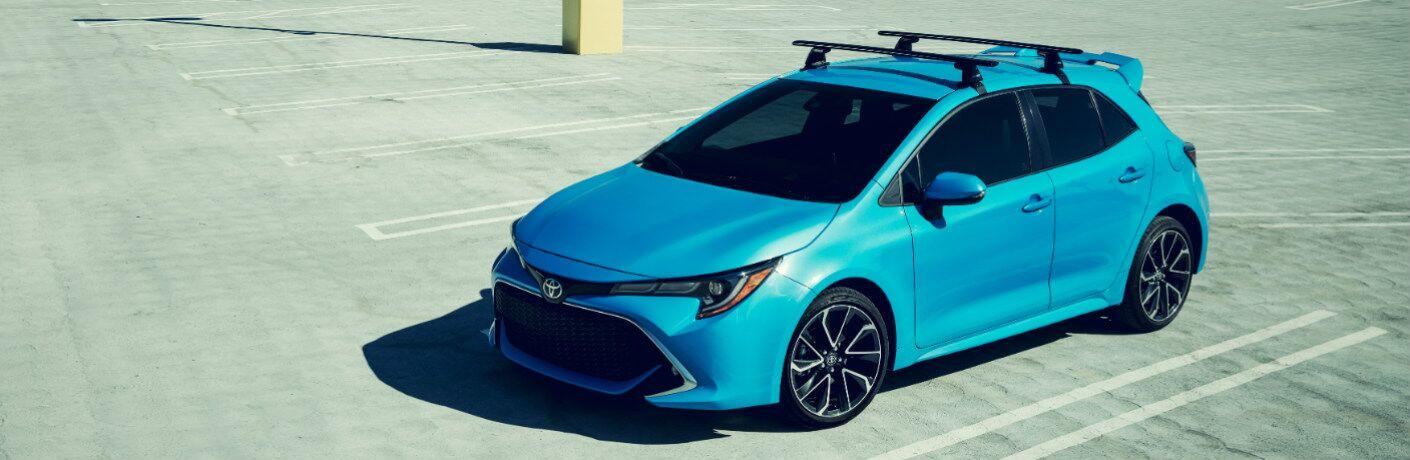 Blue 2019 Toyota Corolla Hatchback in an empty parking lot