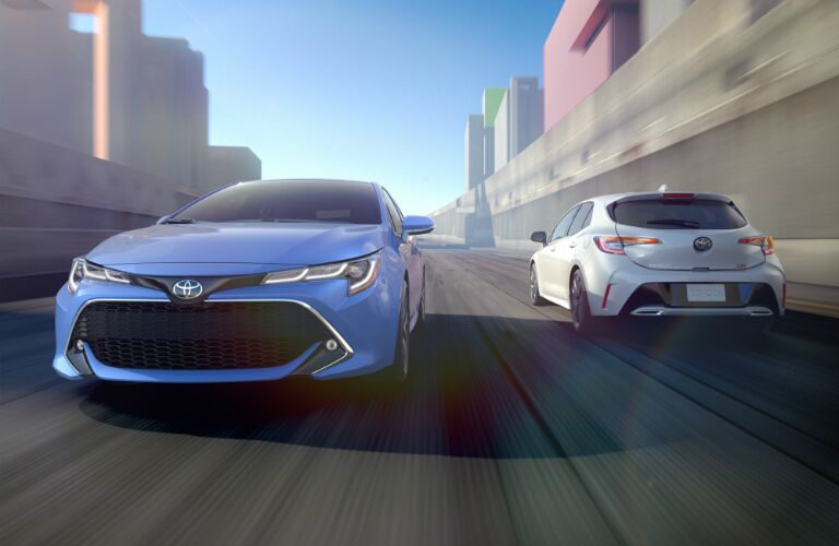 Blue and white 2019 Toyota Corolla Hatchback passing each other