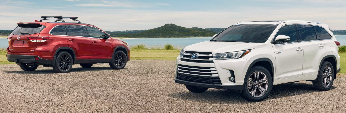 Red and white 2019 Toyota Highlander models parked next to each other