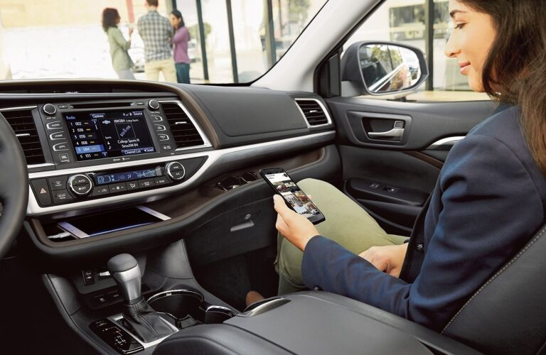 Woman using her phone with the 2019 Toyota Highlander Hybrid infotainment system