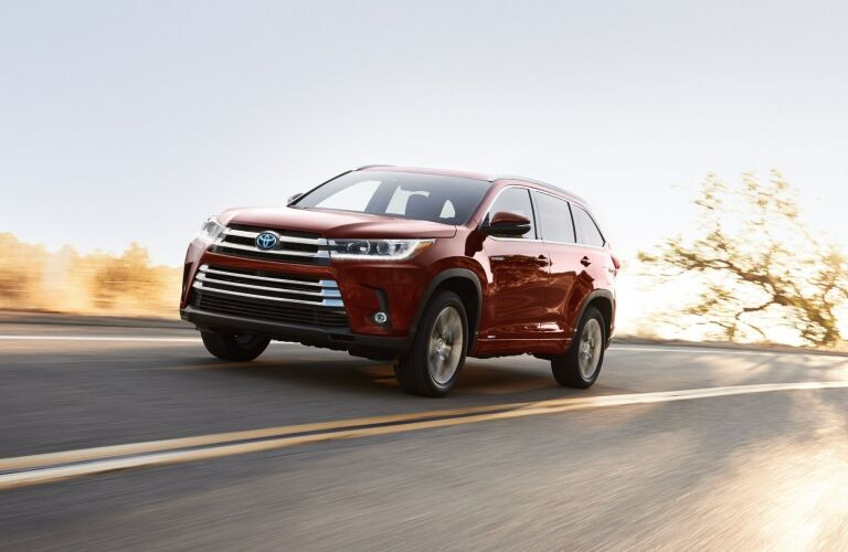 Red 2019 Toyota Highlander Hybrid driving on open road