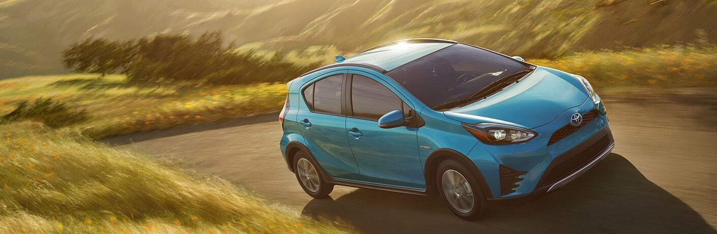 Blue 2019 Toyota Prius c driving through grassy field road