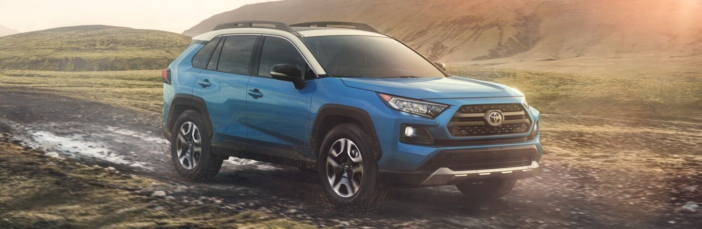 Side view of a blue 2019 Toyota RAV4 driving off-road through mud