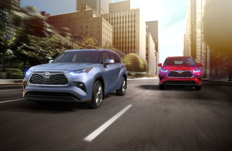 Two 2020 Toyota Highlander models driving on city road