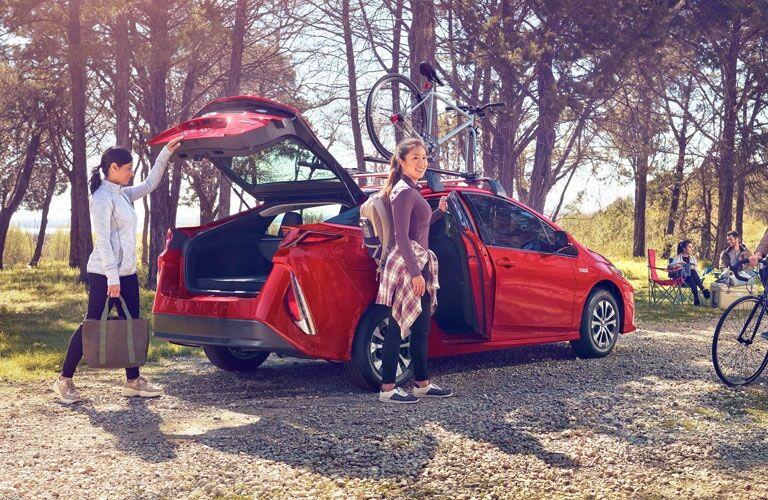 People unpacking the 2020 Toyota Prius Prime at campsite