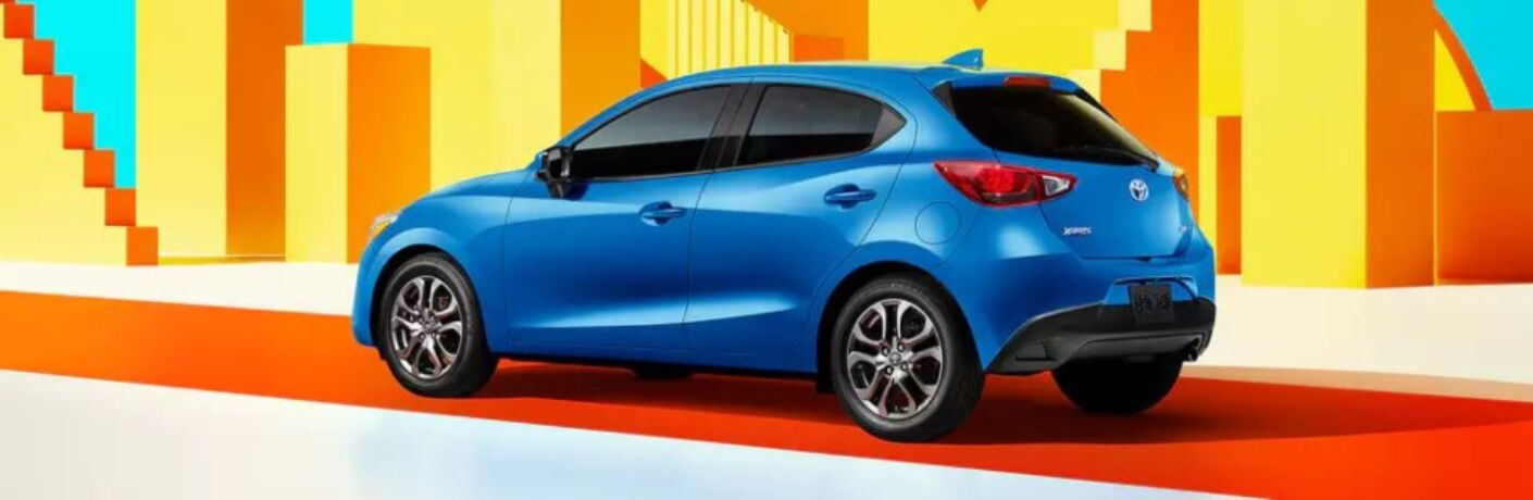 Blue 2020 Toyota Yaris Hatchback in front of colorful background