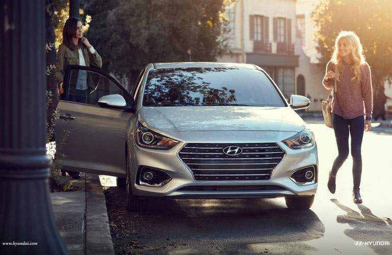 front view of two women beside a 2018 Hyundai Accent