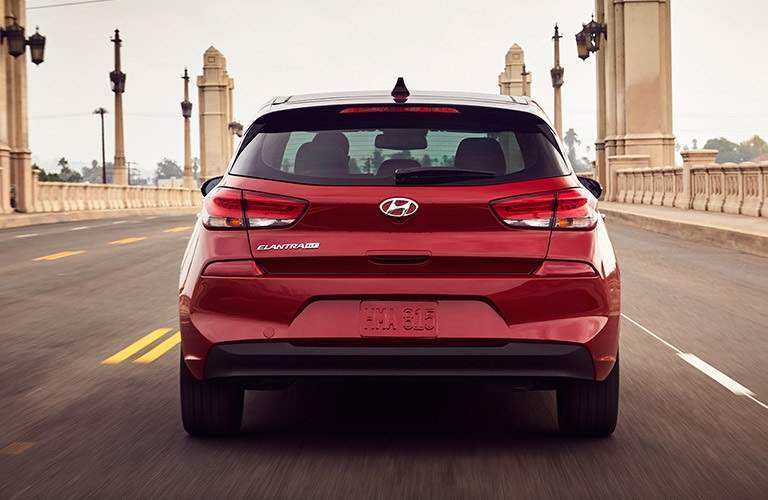 rear view of a red 2018 Hyundai Elantra GT driving over a bridge