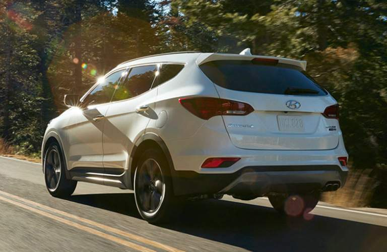 rear side view of white 2018 Santa Fe Sport driving on open road