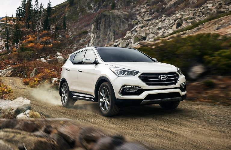 white 2018 Hyundai Santa Fe Sport driving off-road
