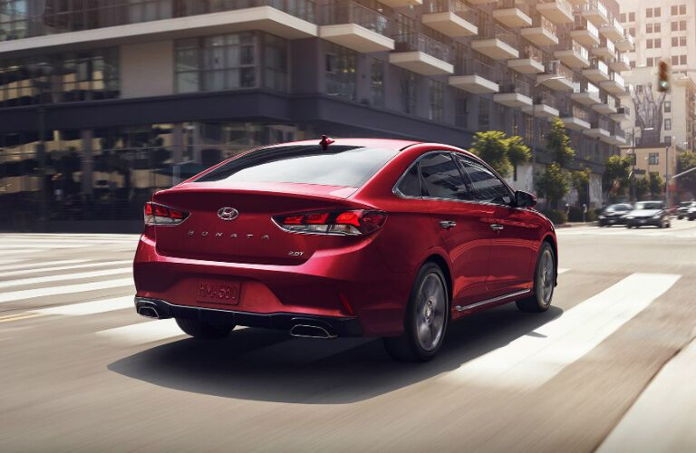 Red 2018 Hyundai Sonata driving on busy street