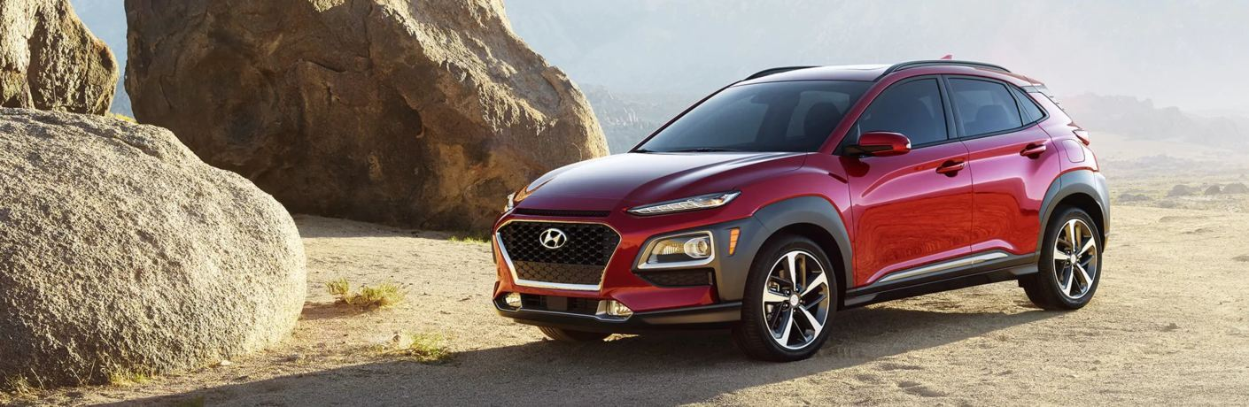 Red 2019 Hyundai Kona driving near big rocks