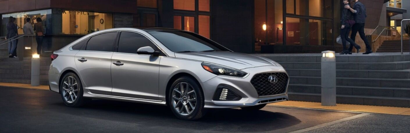 Silver 2019 Hyundai Sonata parked outside of building at night