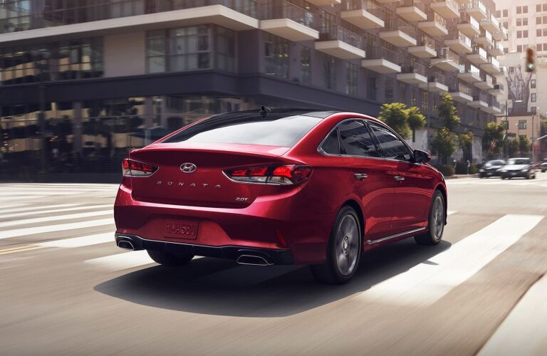 Red 2019 Hyundai Sonata driving on city street