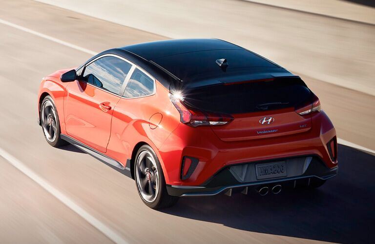 Rear driver angle of an orange 2020 Hyundai Veloster driving down a road
