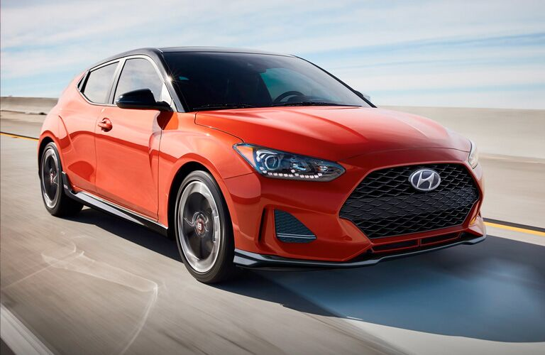 Front passenger angle of an orange 2020 Hyundai Veloster driving down a road