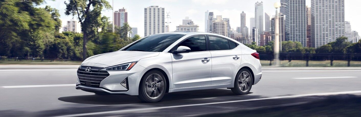 White 2020 Hyundai Elantra driving past city