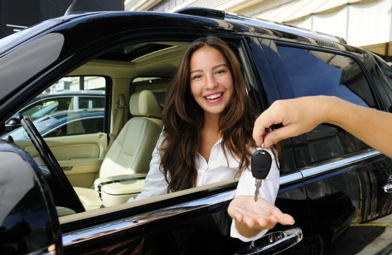 Woman receiving keys to a new car