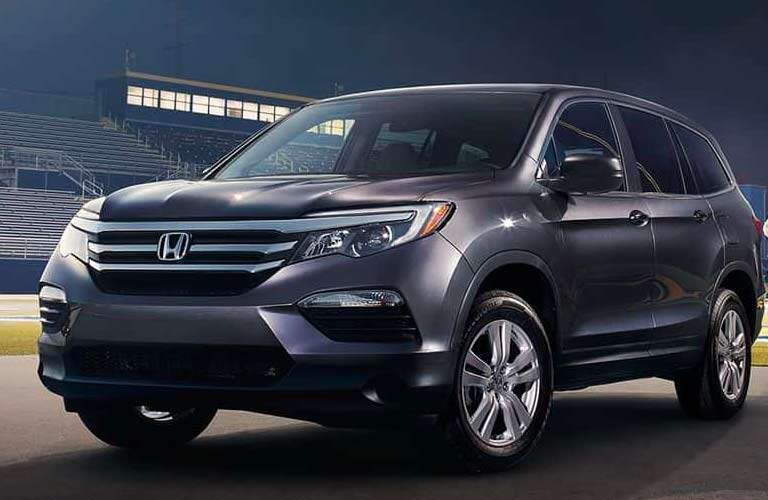 dramatic side view of a 2017 Honda Pilot LX parked in a high school sports stadium