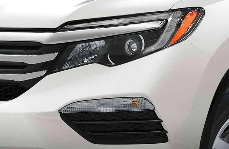 front headlight closeup of a white 2017 Honda Pilot LX