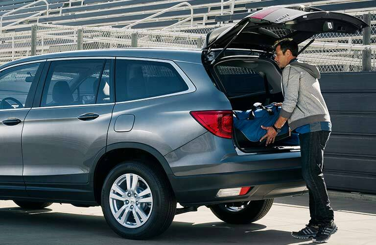 man putting a suitcase into the rear of a 2017 Honda Pilot LX