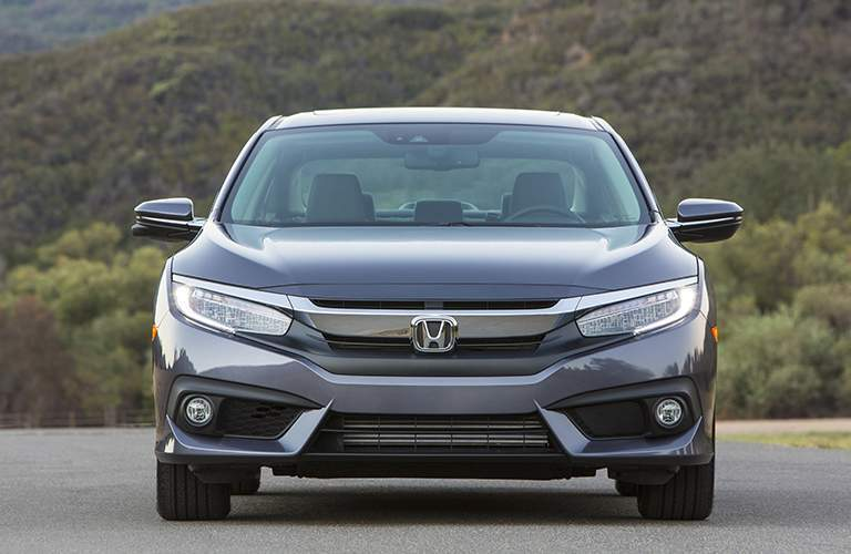 front view of a grey 2018 Honda Civic parked in front of a hill