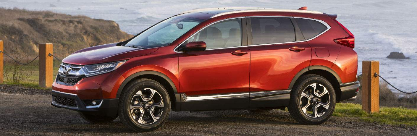 side view of a red 2018 Honda CR-V with cliffs and water in the background