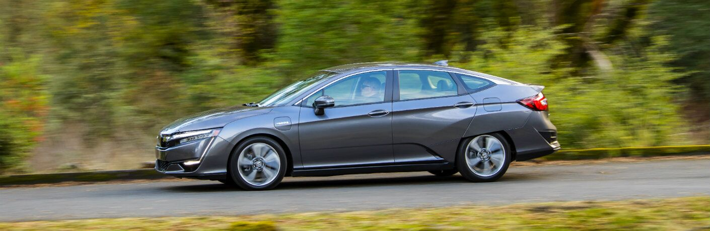 side view of the 2018 Honda Clarity Plug-in Hybrid driving past blurred trees and bushes