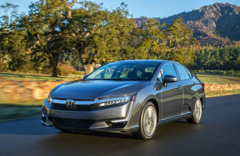dark gray 2018 Honda Clarity Plug-in Hybrid driving on the road in front of trees and mountains