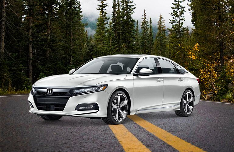 side view of a white 2019 Honda Accord in the forest on a road