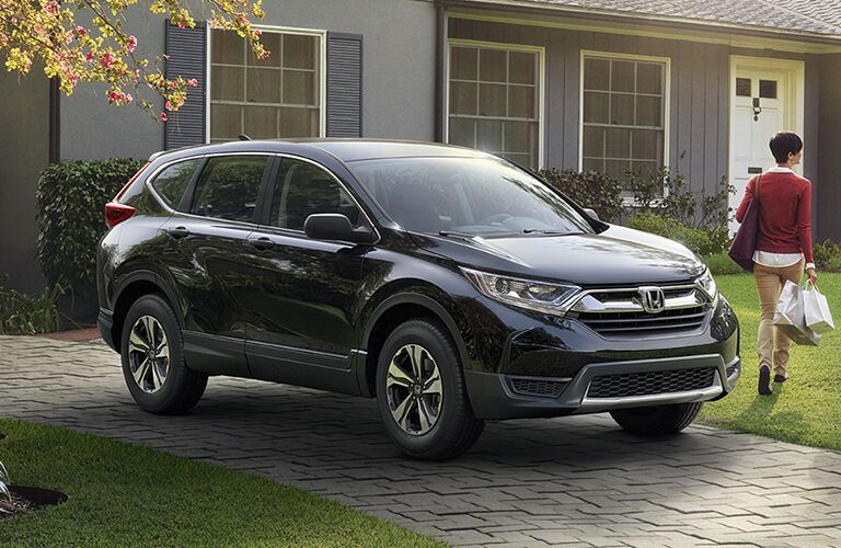 2019 Honda CR-V exterior front fascia and passenger side parked in brick driveway in front of house with person walking towards house