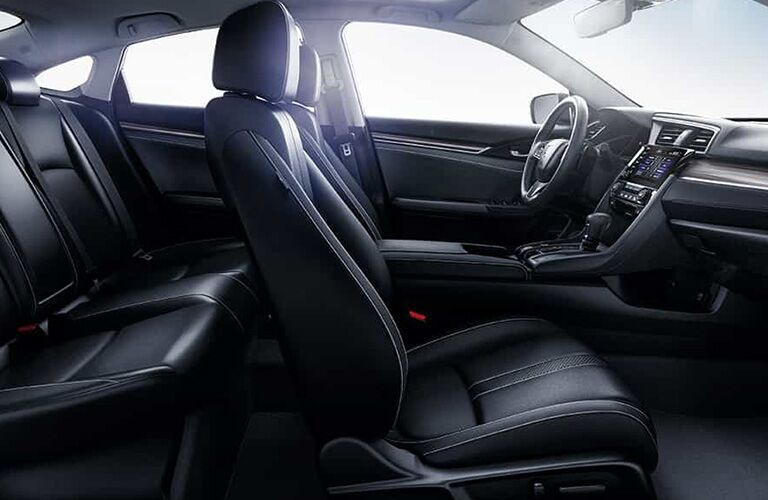 2019 Honda Civic Touring interior front cabin side view of seats partial rear seats steering wheel and dashboard