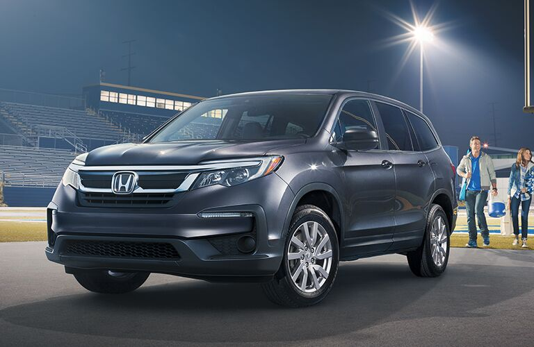 2019 Honda Pilot exterior front fascia and driver side parked in empty stadium with man walking towards back