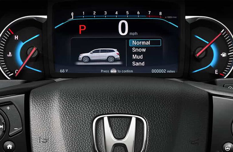 2019 Honda Pilot interior close up of partial steering wheel and drive mode on screen