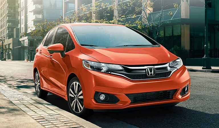 red 2017 Honda Fit on the road in front of a bridge