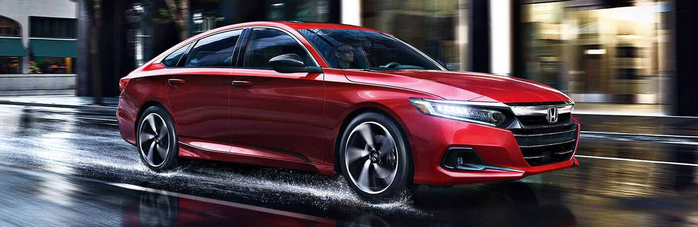 Red 2021 Honda Accord driving on wet road