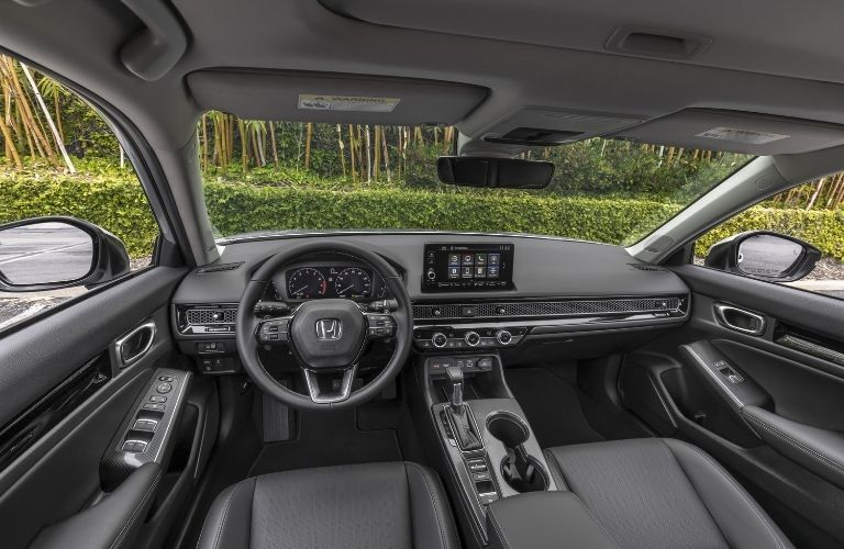 A close-up of the steering wheel and dashboard in the 2022 Honda Civic