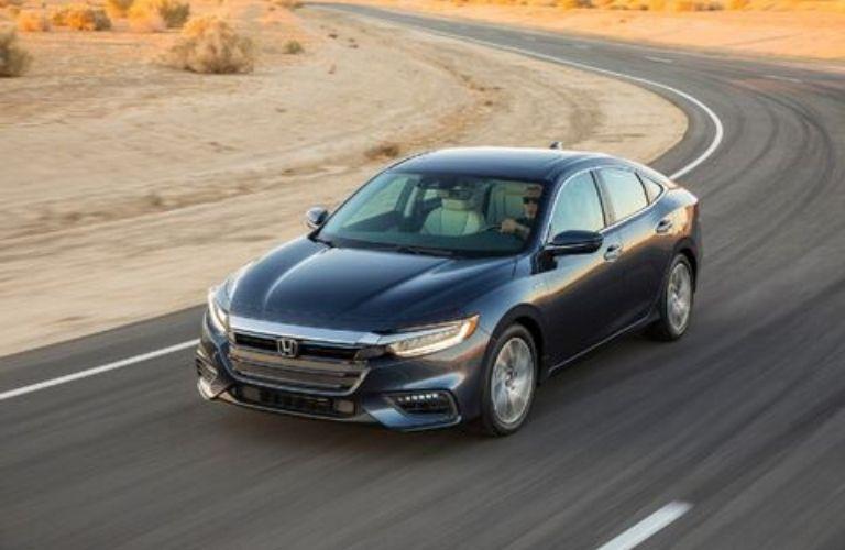 2022 Honda Insight Crystal Black Pearl driving around curve in desert